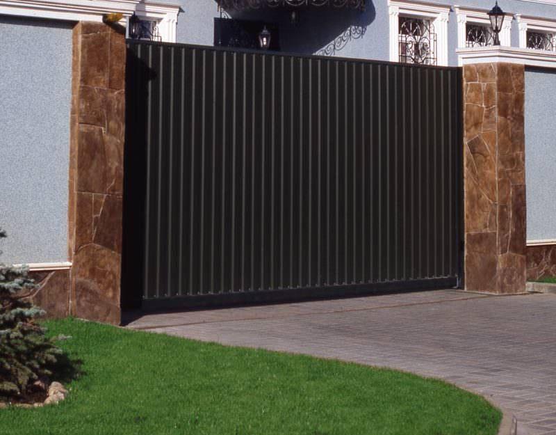 Монтаж сдвижной воротной конструкции предполагает строго вертикальную установку опорных столбов и их последующее бетонирование с минимальным заглублением на метр