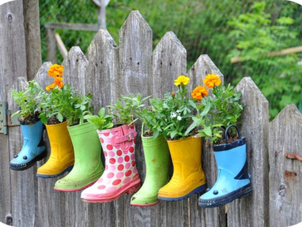 Украшаем дачный забор неординарными цветочными емкостями из обуви
