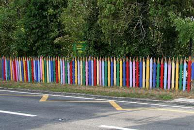 Забор в виде цветных карандашей создается из бревен или даже досок, которые обрезаются сверху по виду заточки и просто окрашиваются в разные цвета