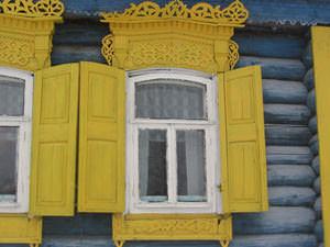 Обыкновенные двустворчатые ставни на деревянном доме
