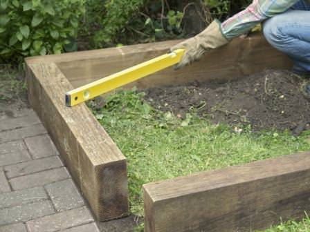 Предварительная установка деревянных стенок грядки и проверка уровней