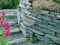 Грядки, как и подпорные стенки, можно строить из камня